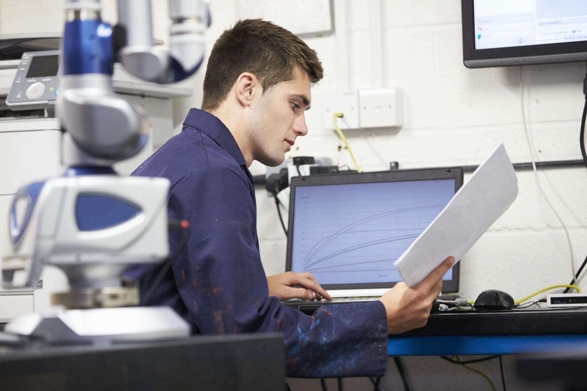Man looking at computer in factory - maintenance tracking software - MATE PCS