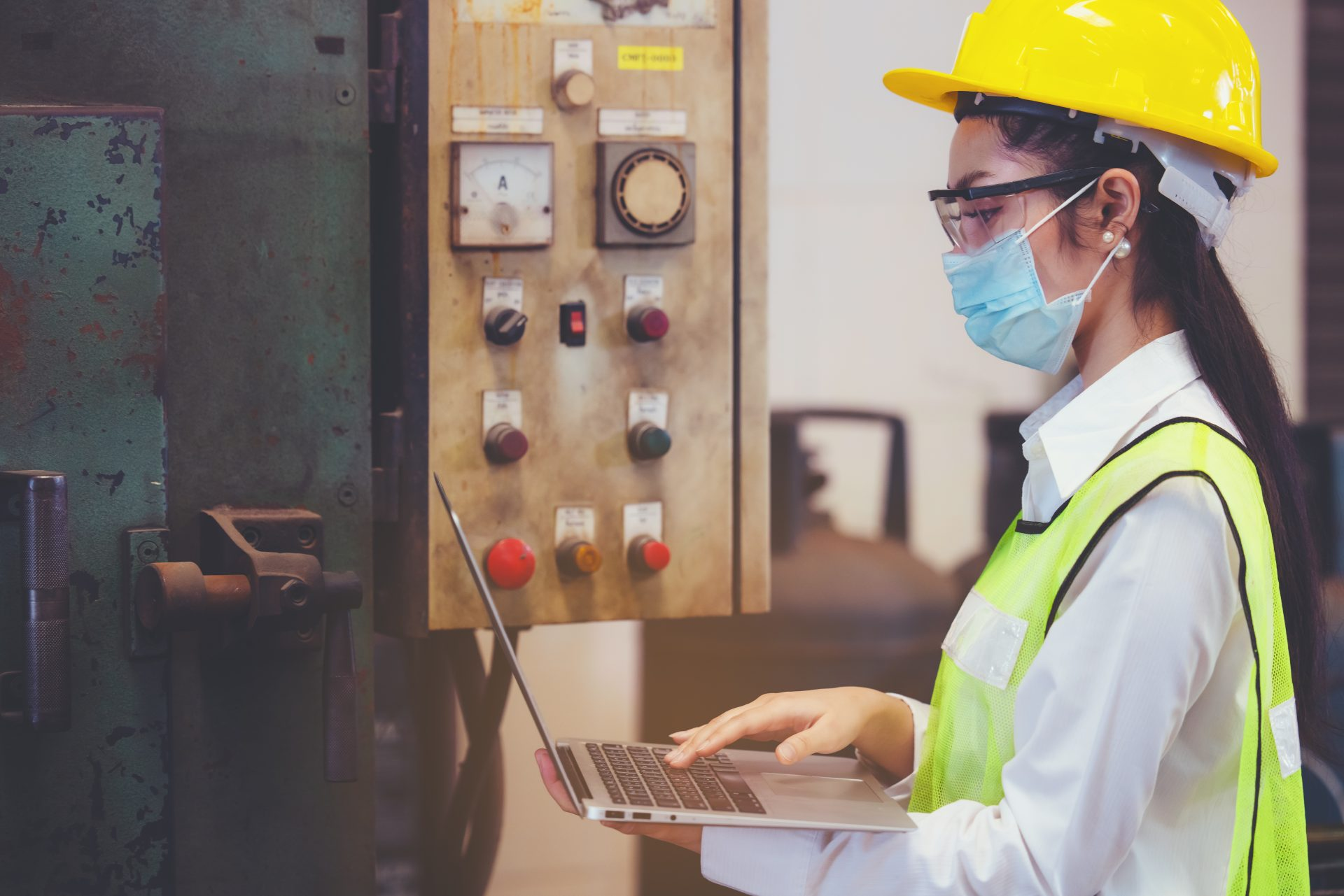 Woman with mask examines laptop at factory - maintenance management systems - GP MATE