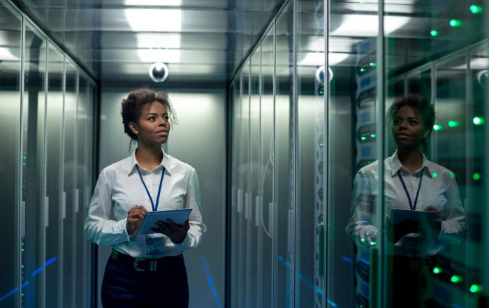 Woman examining computer servers - Maintenance management software - MATE PCS