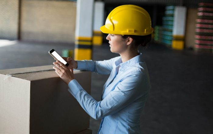 Woman in hard hat using phone - Mobile Work Order Management - MATE PCS